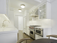 All White Kitchen With Stainless Appliances And Small Table