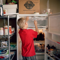 A young blonde haired boy cleans the freezer by hammering at a thick layer of ice in the refrigerator with a meat tenderizer in