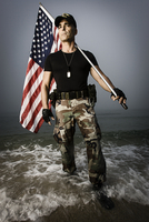 Patriotic US soldier holding American Flag while standing at edge of ocean