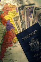 American passport with foreign currency and map of South America