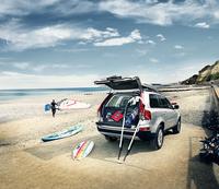 Car on beach with windsurfer