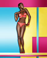 A model with a shaved head wearing bright colored swimwear in front of a geometric brightly colored background