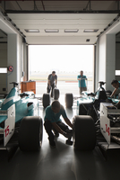 F1 crew team working on race cars
