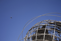 Plane flying over the Unisphere at Flushing Meadows Park