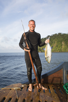 man in wetsuit holding speared fish and spear gun on the deck of a boat