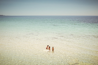 Three young girls standing in shallow crystal clear water of the Adriatic sea, blue summer sky