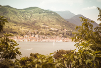View through tree leaves onto a lake surrounded by high mountains, a city along the coastline, Mediterranean summer mood