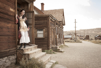 Woman in period dress in western ghost town.