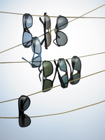 Still life of multiple sun glasses hanging on various strings against a light and blue background.