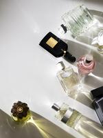 Still life of multiple perfume bottles on white background.