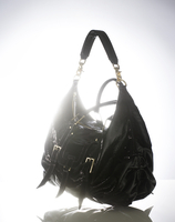 Still life of a black patent leather handbag against a light background.