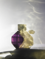 Still life of purple and gold perfume bottle with dramatic shadow play.