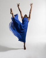 Black female dancer in jazz posture &  blue dress against white background
