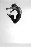 B&W image of Black male dancer jumping against white background