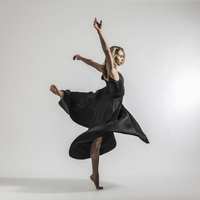 Blonde female dancer in long satin black dress turning in a bellet pose against a white minimal background