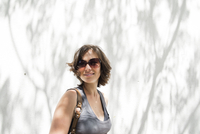 Young woman with sunglasses in front of white wall with patchy shadows of tree.