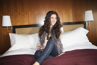 Portrait of young brunette woman sitting on hotel bed with cocktail glass, wearing faux fur boa and open blouse, looking off cam