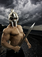 bodybuilder in helmet with sword and stormy background