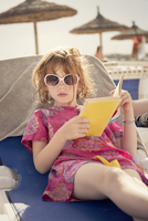 Red head young girl reading book in sunglasses looking in to camera.