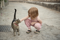 A redheaded girl stroking a cat on the street.