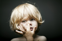 portrait of 4 year old blonde boy in front of dark background in studio setting digging in his nose.