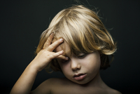 portrait of 4 year old blonde boy in front of dark background in studio setting looking sad.