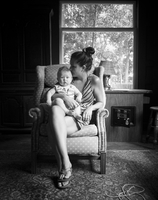 black and white image of thirty something woman holding a baby while sitting in vintage chair by large window.
