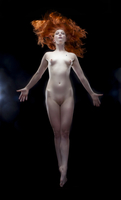 Nude red haired girl floating in studio