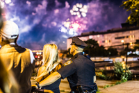 Policeman and blond girl watching a fireworks