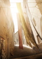 BACK STREETS OF A MEDITERRANEAN HILL TOWN AS FABRICS BLOW IN THE WIND IN WARM SUNLIGHT
