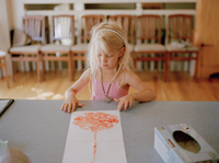 A young blonde girl looks at a paper with the bloody outline of a human placenta on the kitchen counter which her mother is prep