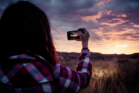 Girl taking a picture of a sunset with a smart phone camera