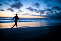 Woman running on the beach at sunset silhouette