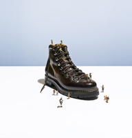 A single hiking boot with miniature people around and on it.