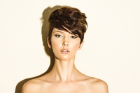 Striking head and shoulders portrait of brunette woman (model) in short hair in studio