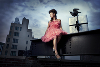 Haute couture model wearing ruffled dress sitting on metal beam with city buildings.