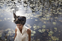 Portrait of a woman with a bird in her hair in front of a lily pond.