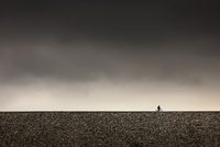Silhouette of bike rider with dark grey storm clouds.