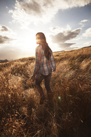 Woman walking thru open field at sunset.