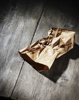 A crumbled brown paper bag on a wood table