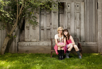 A teenage daughter leans on her mother outside a barn 20055025635| 写真素材・ストックフォト・画像・イラスト素材|アマナイメージズ