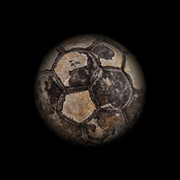 Old football ball with dark background as a planet