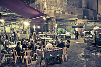 a square in palermo sicilia with peple sitting around eating and drinking