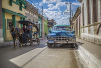 A horse drawn taxi passes a vintage blue car on a colorful street.