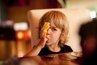 Boy eating pasta off fingers