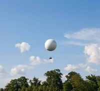 White hot air balloon above trees