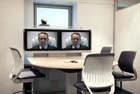 CEO on screens in empty video conference room