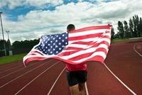Sprinter running with US flag on sportstrack