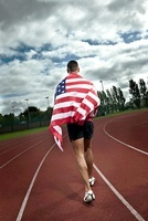 Sprinter running with US flag on sportstrack