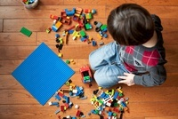 Boy with plastic blocks on floor